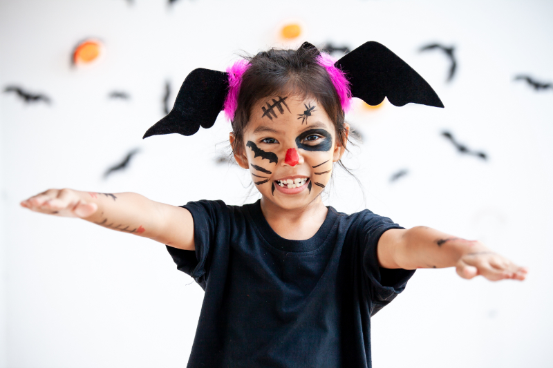 Child girl wearing halloween costumes and makeup.